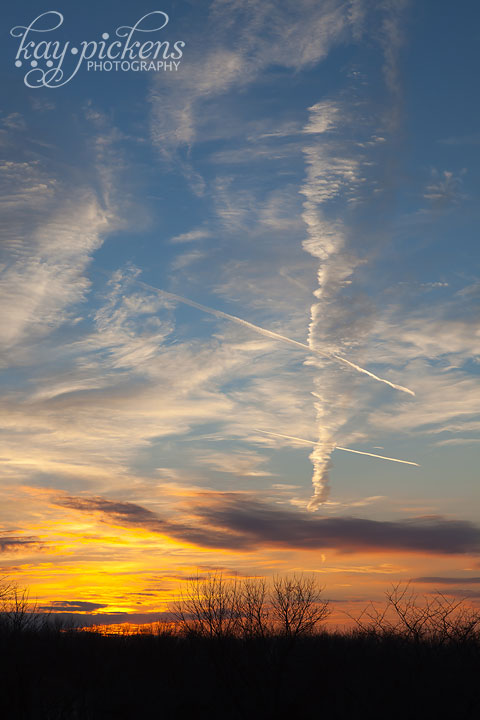 brilliant sunset with pointing contrail clouds